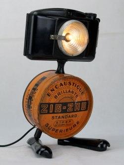 """Sculpture appareil photo en bakélite et boite ZIG ZAG """"encaustique brillante"""", optique de vélo intégré, pied avec une poignée de casserole. Noir et Orange. Bakélite et boite vintage."""