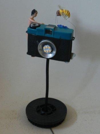 Lampe appareil photo cassé détourné, associée à les objets images de souvenir. Recyclage lumineux.