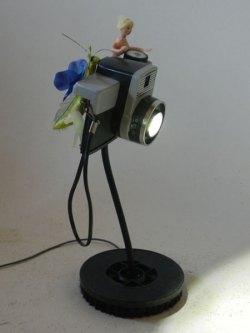 Lampe à poser appareil photo cassé, détourné, associée à les objets images de souvenir. Assemblage lumineux.
