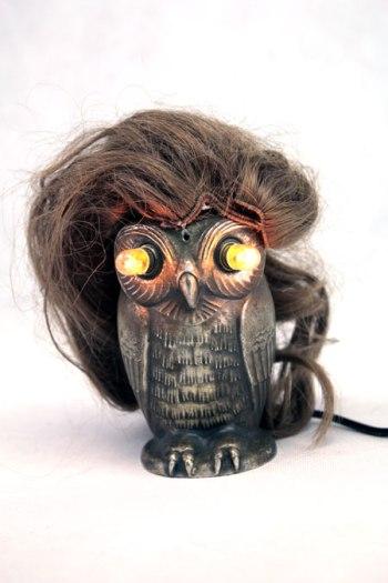 Assemblage d'un cendrier en forme de chouette et d'une perruque de poupée. Recyclage, lumière, upcycling, détournement.