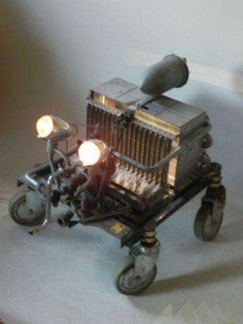 Sculpture véhicule spatial recyclage lumineux. Assemblage d'un intérieur de chaudière sur roulettes, un moteur d'aspirateur et deux optiques de vélo ancien en aluminium.