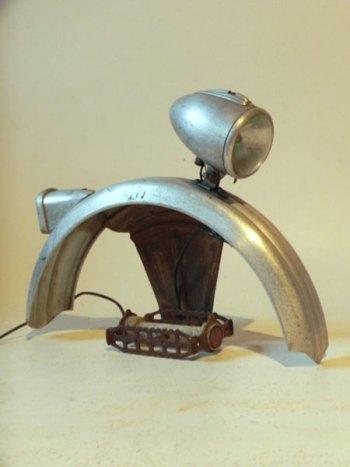 Sculpture détournement pièces de vélo. Assemblage lumineux d'optiques de vélo, un garde boue de vélo enfant, une pédale.