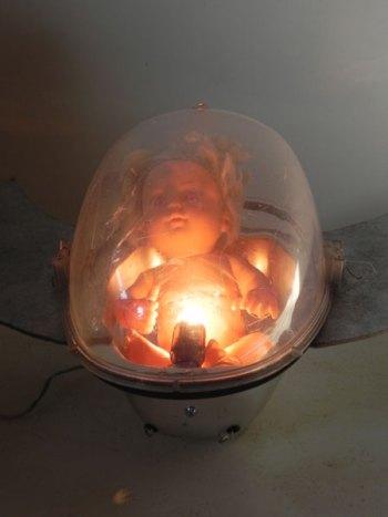 Vaisseau rétrofuturisme assemblage d'un lampadaire urbain et d'une poupée aux yeux rouges.