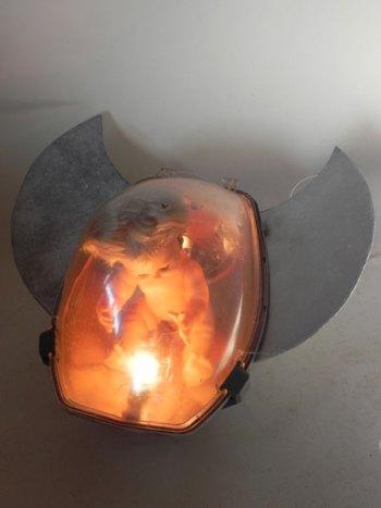 Vaisseau rétrofuturiste assemblage d'un lampadaire urbain, ailes et d'une poupée à bord. Sculpture lumineuse.