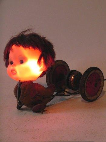 Sculpture assemblage de vieux jouets. jeu de canard cassé, tête de poupée. Lampe sculpture à roulettes.