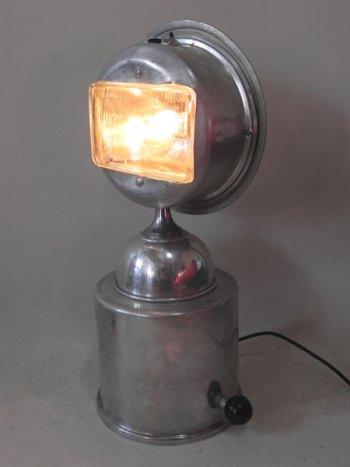 Buste lumineux aluminium et phare. Assemblage de gamelles de camping et un feu avant de voiture.