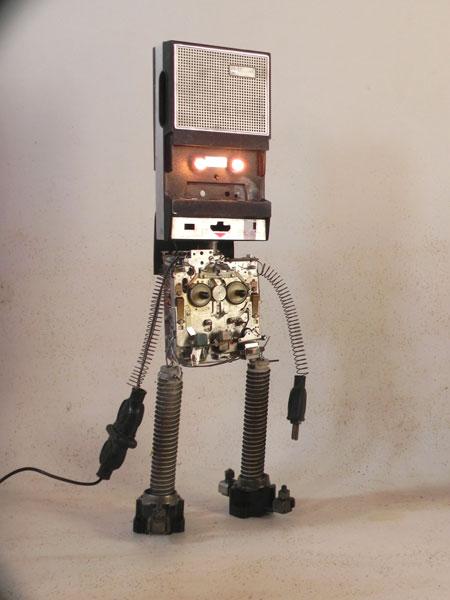 """Robot magnéto lumineux. Lecteur de cassette """"philips"""" démonté et recomposé, avec des éléments de radiateur, et 2 fiches électriques."""