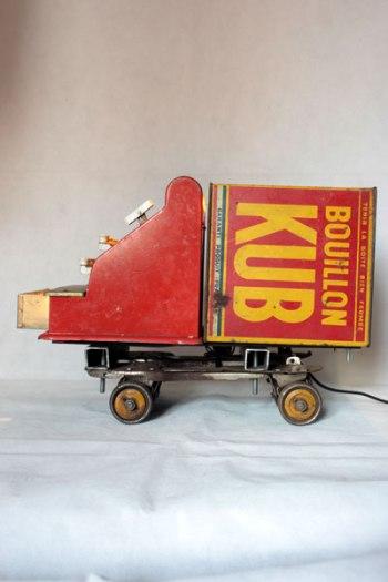 Camion rouge KUB assemblage d'une caisse enregistreuse pour enfants et d'une boite de bouillon KUB, sur deux patins à roulettes.