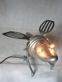 Insecte par assemblage d'objets en alu. Composition: embauchoir, coupe de sport, filtre et ustensiles de cuisine. Recyclage et détournement lumineux.