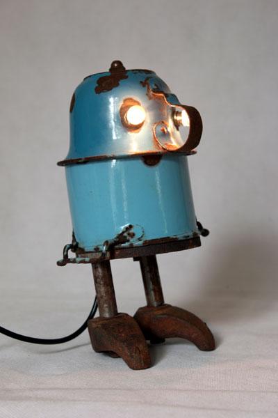 Bonhomme avec tasse et pot en émail bleu rouillé, pièces de machine en fonte. Assemblage de vaisselle en métal.