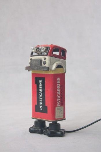"""Personnage lumineux avec un camion et une boite de médicament """"Intesticarbine"""", quincaillerie. métal imprimé, plastique. Rouge. jouet,"""