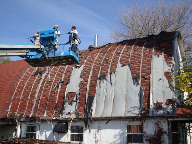 Fall, 2011, Primo Briano and Pollo Casique approach the tattered loft roof