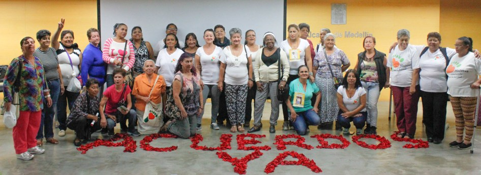 """Members of the Women Walking for Truth gather behind the message """"Accords Now"""" scrawled across the stage with rose petals for an October 14, 2016 event commemorating Operation Orion."""