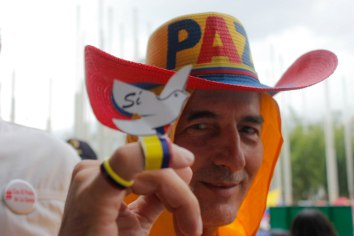 "A Medellín local wears a hat reading ""peace"" and a dove on his finger that reads ""yes."""