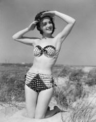 1950s smiling young woman kneeling in grassy sand wearing polka dot bikini shading eyes from sun da/from www.corbis.com
