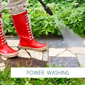 Person in red gumboots cleaning garden alley with a pressure washer