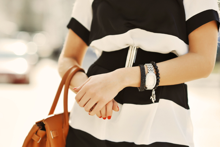 Fashionable woman with handbag in hands - close up