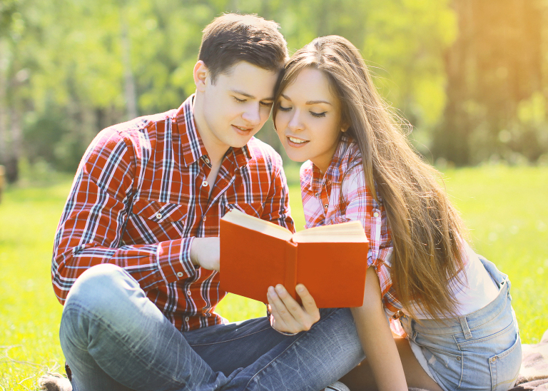 Portrait beautiful young man and girl reading a book in a city p