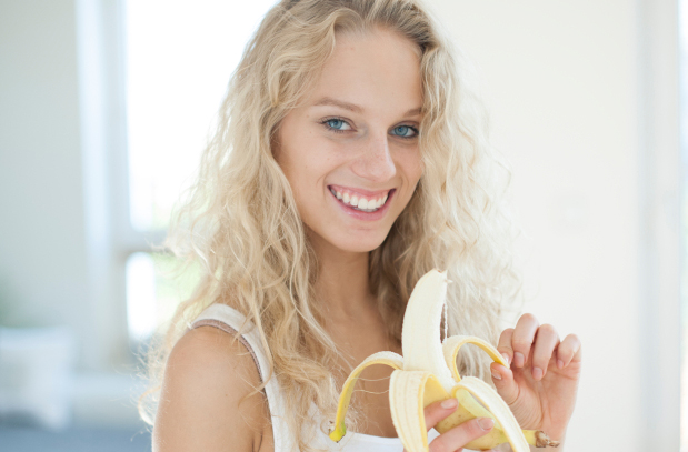 Portrait of young woman peeling banana in house