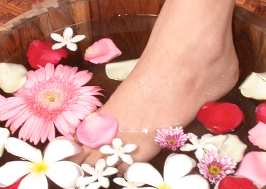 Dipping foot into water with flowers
