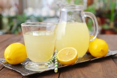 Lemon juice with fresh lemon and mint in glass on wooden background ** Note: Shallow depth of field