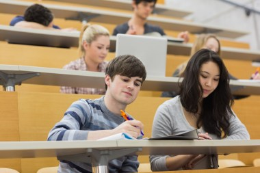 Students listening and taking notes in a lecture hall in college