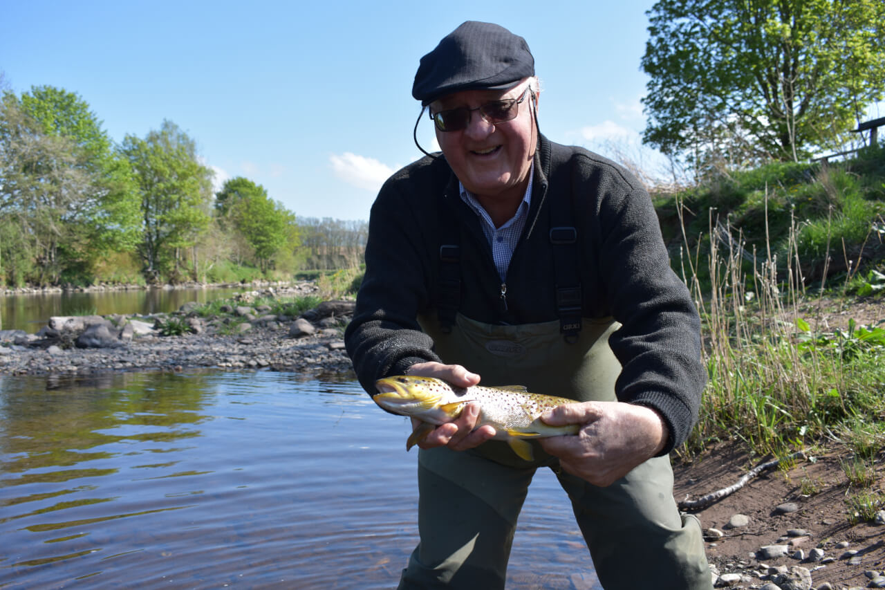 client with brown trout caught during guided fishing vacation