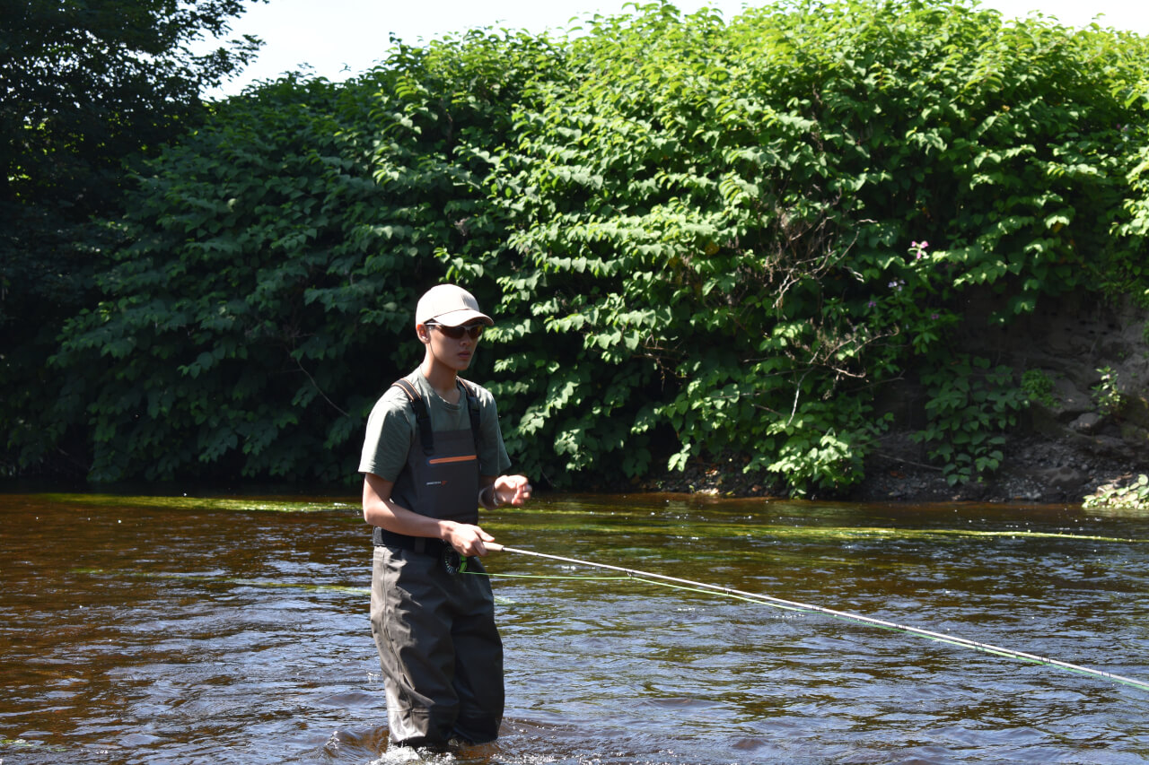young lad learning fly casting on the river during family fishing holiday in scotland