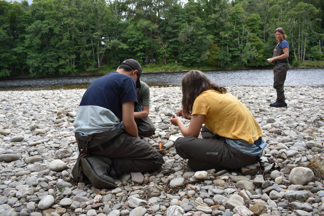 kids making coffee beside river during scotland fishing trip