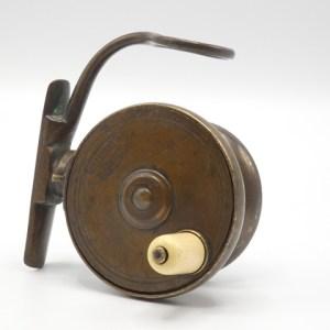 """A Malloch brass 2 ½"""" side casting reel,"""