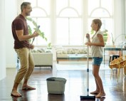 Father and daughter dancing and mopping floors in living room