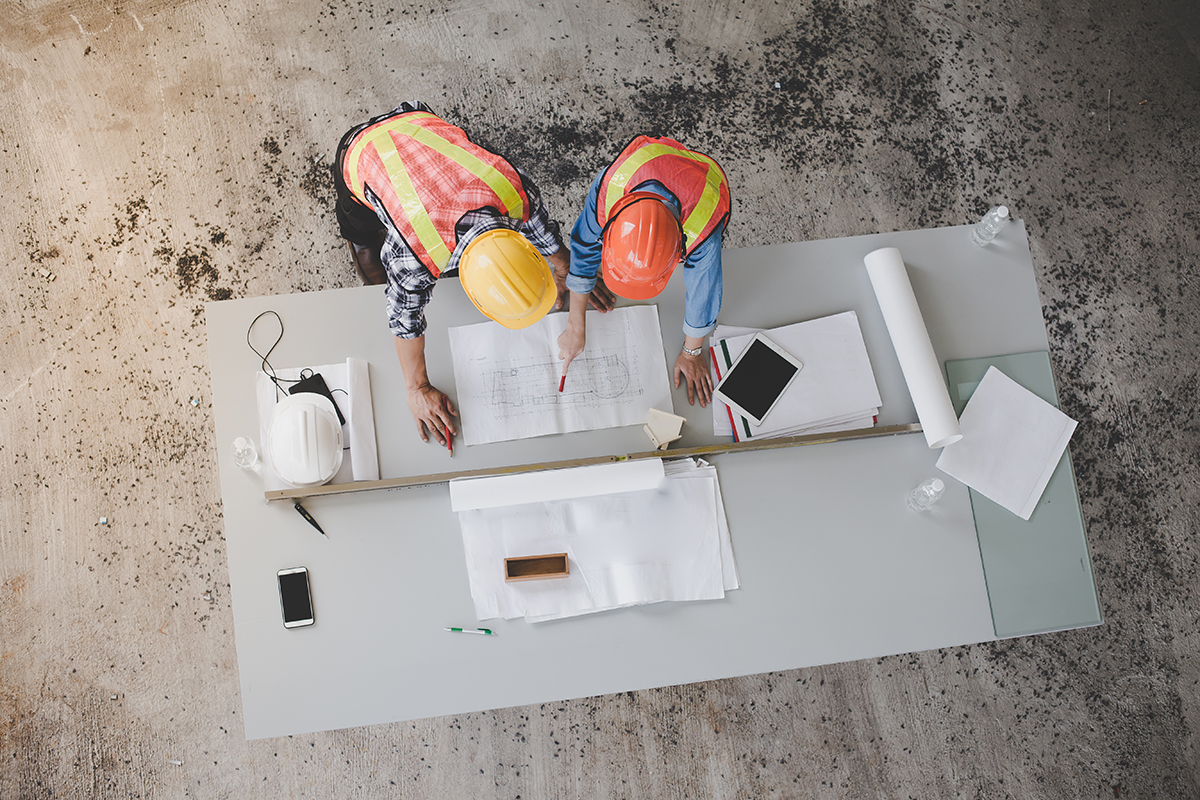 Two workers look over plans on a construction site