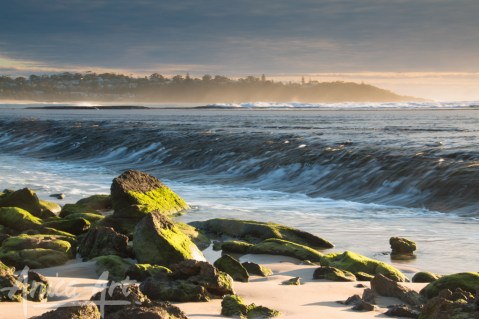 Sunlit mossy rocks with Bannister HEadland in the background
