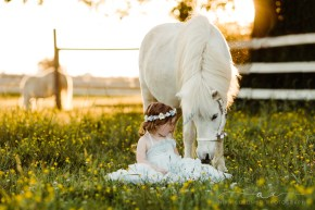 toddler sitting in a field of buttercups in richmond, va while staring face to face with a white unicorn