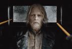 Trata-se de uma captura de tela do trailer de Animais Fantásticos: Os Crimes de Grindelwald. Na imagem, vemos Grindelwald olhando diretamente para a câmera. O bruxo está com uma aparência ruim, já que sua barba não está feita e seu cabelo está desgrenhado. Duas pessoas apontam suas varinhas para ele. Eles parecem estar dentro de uma carruagem.