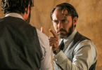 Dumbledore (Jude Law) se olha no espelho de Ojesed e está com o dedo apontado aparentemente para si. Ele está sério.