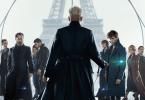 Pôster final de Animais Fantásticos: Os Crimes de Grindelwald. Ele tem Grindelwald, de costas e centralizado, segurando a varinha das varinhas. De frente pra ele e encarando o observador, os personagens Leta, Teseu, Dumbledore, Nagini, Credence, Tina, Newt, Queenie, Jacob e Yusuf Kama. No fundo branco, atrás, é possível ver a torre Eiffel, também centralizada, e o símbolo das Relíquias da Morte.