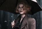 Imagem promocional de Os Crimes de Grindelwald. Nela, vemos Queenie olhando para algo à sua frente parecendo preocupada. Está chovendo no local e ela segura um guarda-chuva.