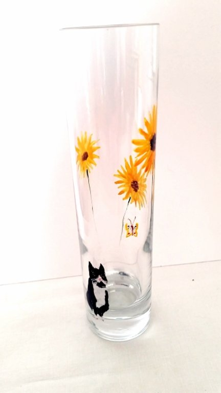 A small vase with a balcka nd white cat watching a butterfly and sunflowers