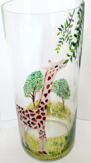 A Giraffe vase hand painted with a giragge reaching up to leaves on a tree