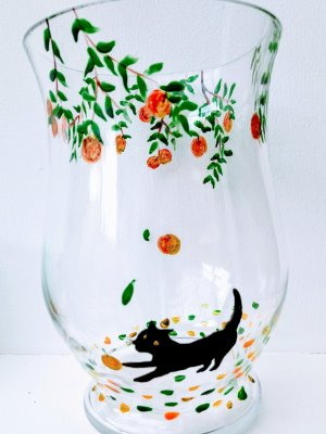 Black cat hurricane vase painted with the cat playing under an apple tree