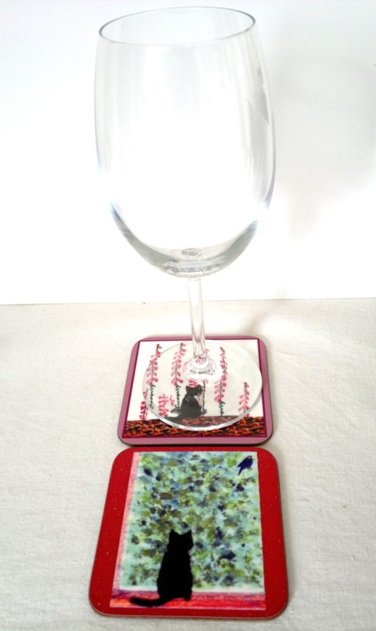 Photo of two coasters with cats in a garden and a wine glass
