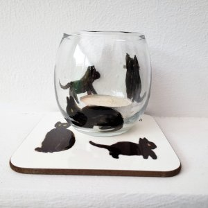 A black cat candle holder and coaster set