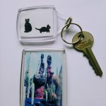 A keyring with 2 black cats and fridge magnet with a black and white cat in a cactus garden