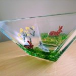 Large square glass bowl with three rabbits and flowers. Photographed from a corner