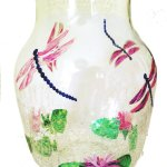 Vase with waterlilies and pink dragonfly flying overhead.