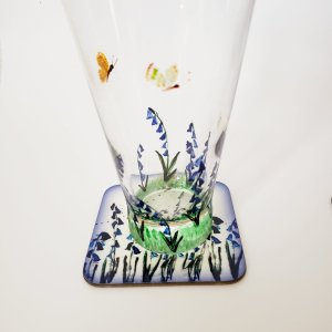 Hand painted glass with bluebells and Butterflies, photographed with a matching coaster