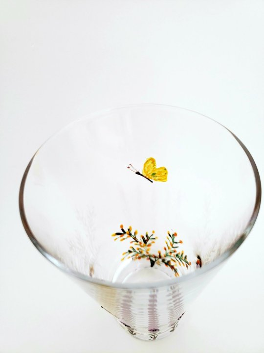 inside of a hand painted glass with gorse and a butterfly