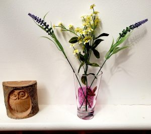 Small vase painted with a tree in blossom and brown owl. Photographed with an owl ornament and flowers