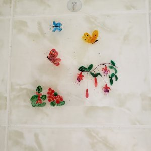 An original glass painting with 3 butterfly and fuscia flowers. Photographed on a bathroom tile